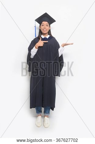 Full length   Portrait of female student wearing a gown and a hat graduating from college looking at camera show welcome hand gesture
