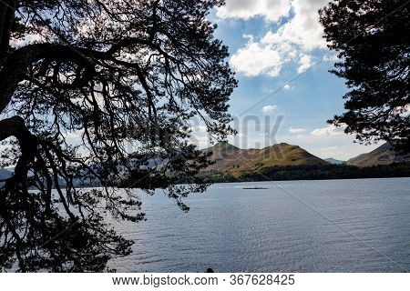 Derwent Water With Cat Bells In The Lake District Framed By Trees.