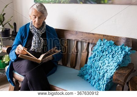 Senior Woman Alone At Home Reading An Old Book