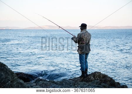 Fisherman catches fish on the rocks in the morning in spring