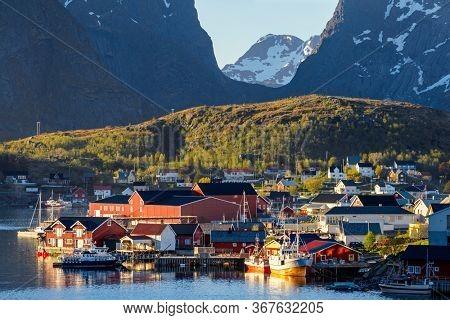 Famous Norwegian Reine Fishing village  , Lofoten Islands,  Norway.Mountains With Snow In Background, Summer midnight sun