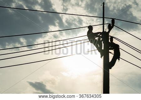 Electrician Worker Climbing Electric Power Pole To Repair The Damaged Power Cable Line Problems Afte