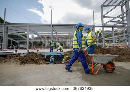 Bucharest, Romania - May 8, 2020: Details With A Construction Worker Pushing A Wheelbarrow On A Cons