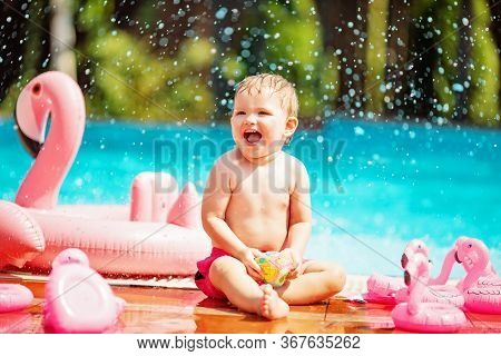Pretty Toddler Boy Sitting On The Edge Of The Swimming Pool And Laughing Next To The Pink Flamingo S