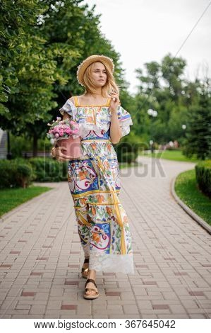 Beautiful Blonde Woman With Pink Box Of Flowers Walks In The Park And Looks Away