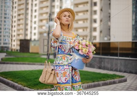 Beautiful Blonde Woman With Pink Box Of Flowers Walks And Looks Away