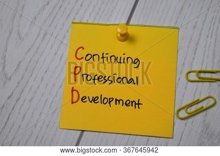 Continuing Professional Development Write On Sticky Note Isolated On Wooden Table.