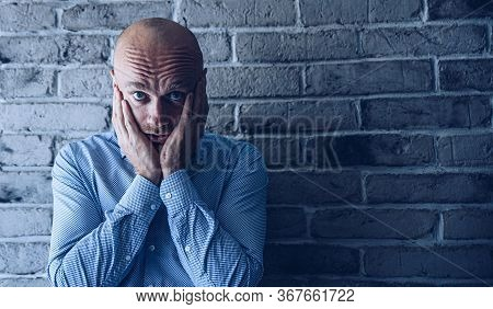 Despressed Man. Worried Man In Shirt Standing In Front On Grey Brick Wall.