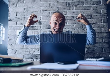 Angry And Furious Man Working On Laptop Computer