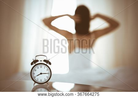 Woman Stretching Hands In Bed After Wake Up, Sun Flare . Brunette Entering A Day Happy And Relaxed A