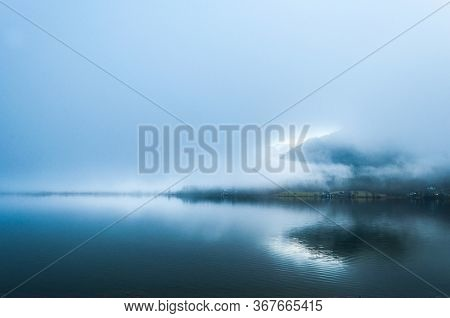 Humid And Foggy Morning On The Cold Alpian Lake Between The Mountains