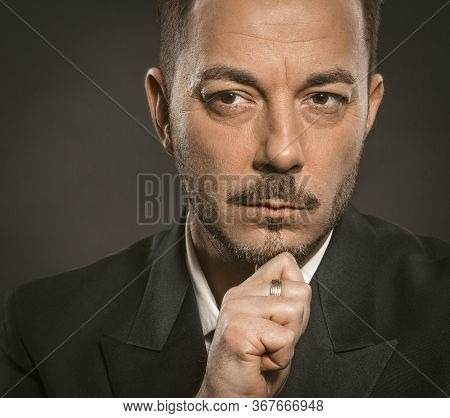 Thoughtful Businessman. Handsome Serious Man Touching His Chin With Hand. Close Up Portrait Of Mid A