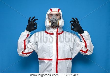 Man In Chemical Protective Suit Shows Okay Sign On A Isolated Background, Epidemiologist, Biologist,