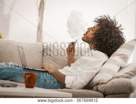 Young Man Smoking Of Electronic Cigarette At Home. Arabic Guy Smokes E-cigarette Resting At Sofa Whi