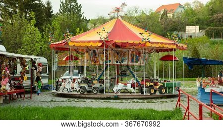 Childrens Attraction Carousel. Bright Multi-colored Carousel On The Nature In The Fresh Air Outdoors