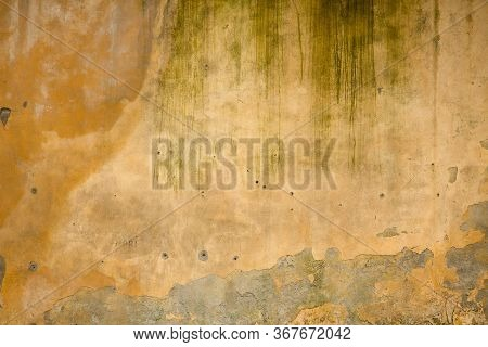 Texture Of Old Yellow Stucco Wall. Ancient Wall With Fallen Stucco And Bullet Holes. Texture And Bac