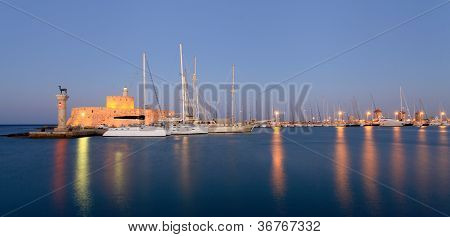 Rhodes Harbor And Windmills In Greece At Sunset