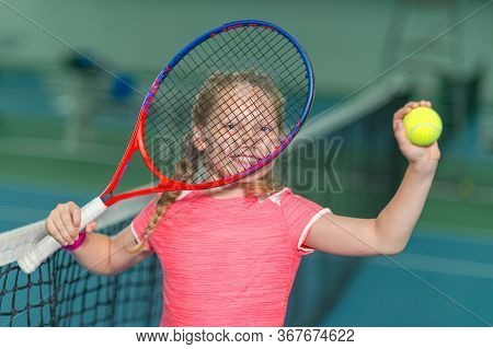 A Happy Playful Girl Smiles Mischievously On The Tennis Court With A Racket.