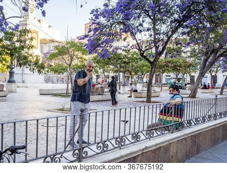 Malaga / Spain - May 18th, 2020: People Smiling With Lowered Face Masks, Coronavirus, Phase One, Sun