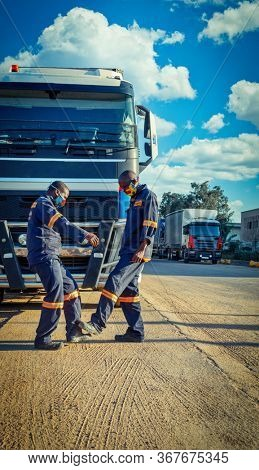 African truck drivers wearing a masks for protection against virus, greet each other with a foot salute