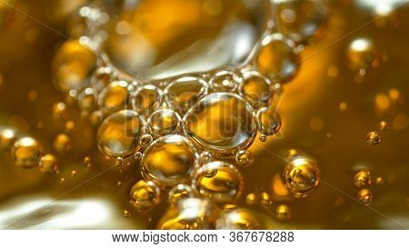 Super Slow Motion Shot of Splashing Oil on Golden Background