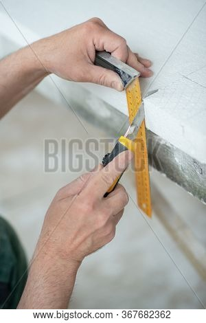 Styrofoam, seiling mounting. A man cuts foam. Warming. Repair in the house. DIY repair. Work with polystyrene foam, insulation of walls and ceiling