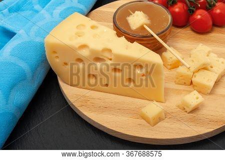 Yellow Maasdam Cheese, Triangular Piece Cheese With Holes, Saucer With Honey, Tomato, Blue Napkin Wo