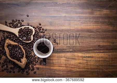Black And Brown Coffee Beans With Cup Of Hot Drink On  Wooden Table, Top View Copy Space