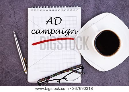 Ad Campaign, Business Concept. Notebook On An Grey Table With A Cup Of Coffee, Pen And Glasses.