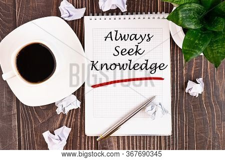 Always Seek Knowledge, An Inscription In A Notebook On A Wooden Table With A Pen And A Cup Of Coffee