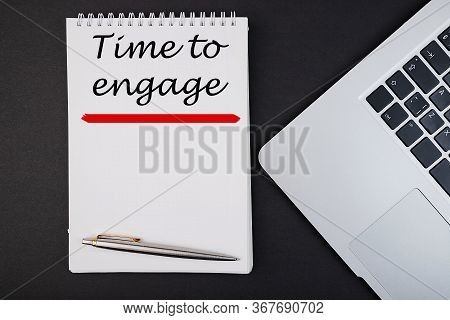 Text, The Word Time To Engage Is Written In A Notebook Lying On A Black Table With A Pen And Laptop.
