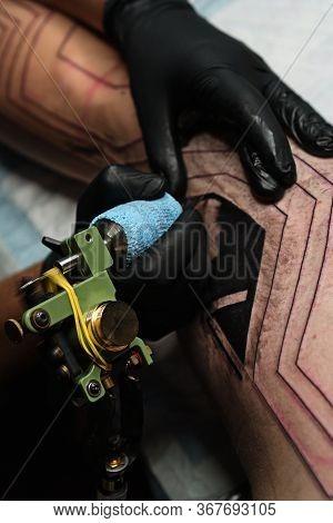 Professional Tattoo Artist Makes Tattoo On Man Leg. Process. Introduces Black Ink Into Skin Using Ne