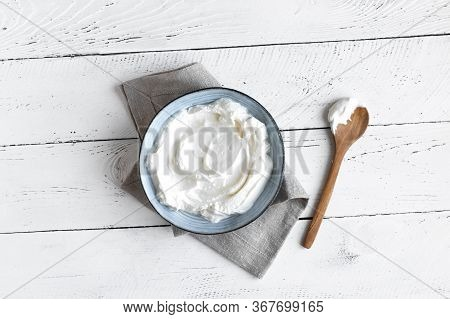 Homemade Yogurt In Bowl On White Wooden Table, Top View, Copy Space. Organic Plain Greek Yogurt For