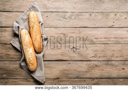Fresh Baguette Bread On Wooden Background. Homemade French Two Baguette Loafs, Top View, Copy Space.
