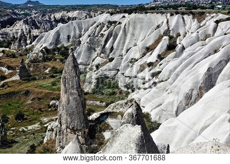 The Amazing Landscape Of Cappadocia. The Valley Is Surrounded By White Folded Slopes Of The Mountain