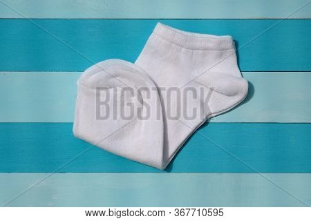 White Cotton Socks On A Blue Wooden Background. White Short Socks For Sports Top View. New White Soc