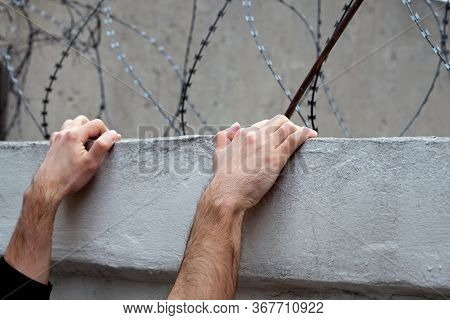 Men's Hands On A Concrete Fence Against A Background Of Barbed Wire.  Trying To Escape From Prison.