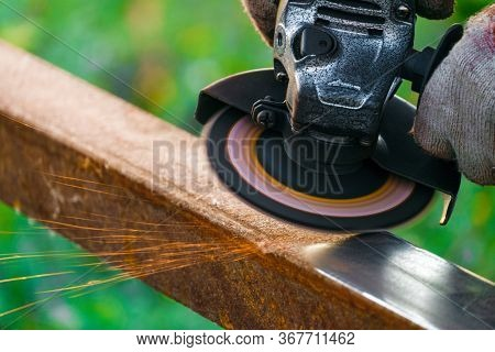 Worker Cleans Rust On Steel Closed Profile Using An Electric Wheel Grinding Machine. Sparks Fly From