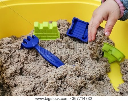 A Child Plays With Kinetic Sand: Closeup Of A Child's Hand And Sand. Sand Is A Natural Color. Sand I