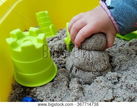 The Child Makes Of A Sandyman From Kinetic Sand. Pictured Is A Child's Hand Holding Sand And Plastic