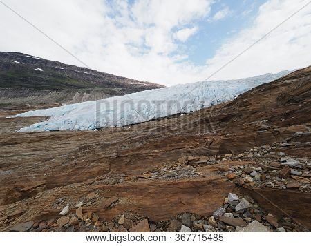 View To Part Of Scenic European Svartisen Glacier Tongue In Nordland County In Norway, Cloudy Sky In