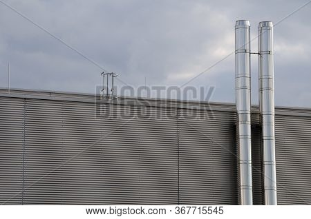 Metal Facade Of An Industrial Building With Two Chimneys Of Stainless Steel