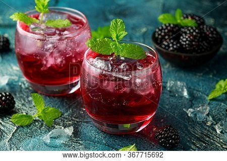 Refreshing Blackberry Cocktail With Ice And Mint On Rustic Background