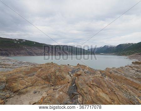 Stony Cliff And Austerdalsvatnet Lake Landscapes Near European Svartisen Glacier In Nordland County