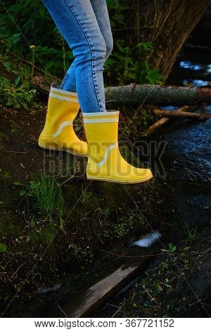 Woman In Yellow High Boots Is Walking Through The Little Brook.