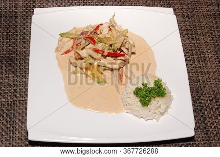 Rice Served With Chicken With Vegetables And Sauce On The White Plate