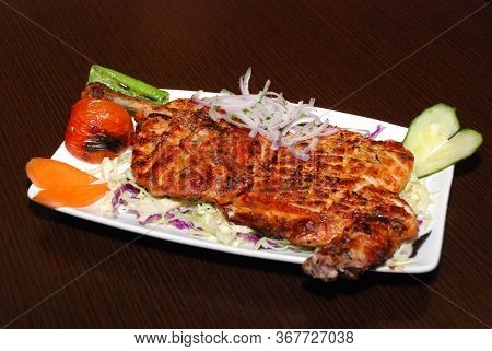Grilled Half A Chicken With Cabbage, Tomato, Green Pepper And Onion On The White Plate. Selective Fo