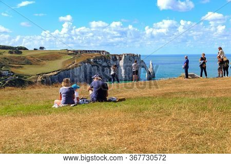 Etretat, France - September 1, 2019: Tthese Unidentified People Rest And Enjoy The Views Of The Coas