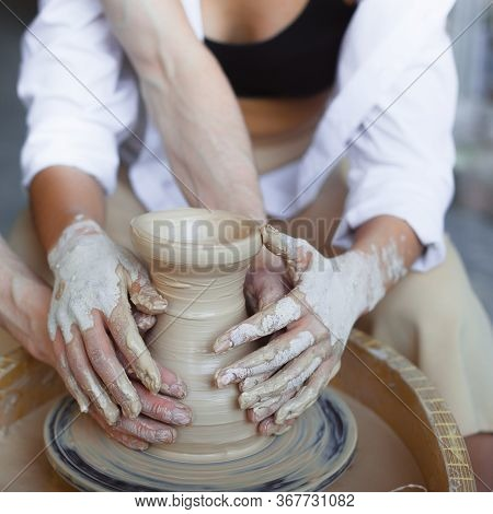 Old Hand Experienced Male Potter Working With Female Apprentice. Working With Clay Lump On Potters W