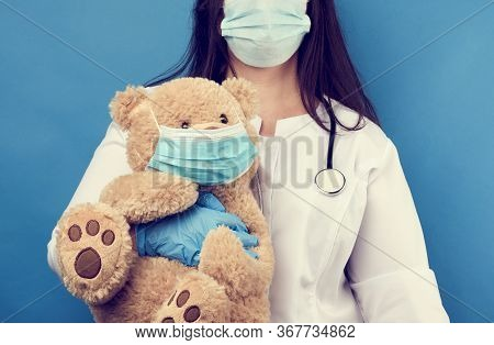 Woman Doctor Pediatrician Holds Brown Teddy Bear In Hand In White Medical Disposable Mask, Concept O